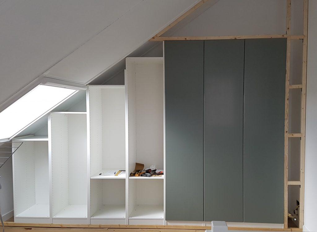 Kastenwand onder een schuin dak met kasten van Ikea Pax