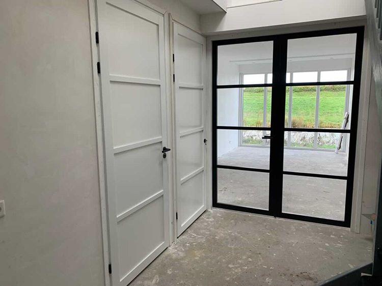 Zwarte glazen deuren naar de woonkamer